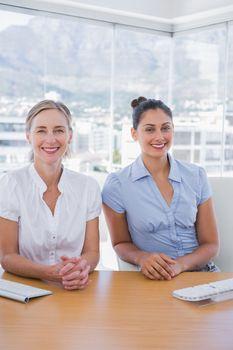 Happy businesswomen sitting side by side