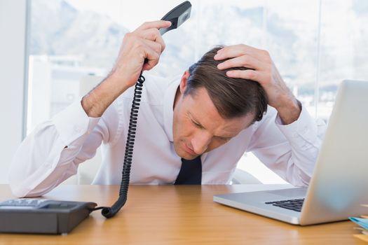 Annoyed businessman holding the telephone