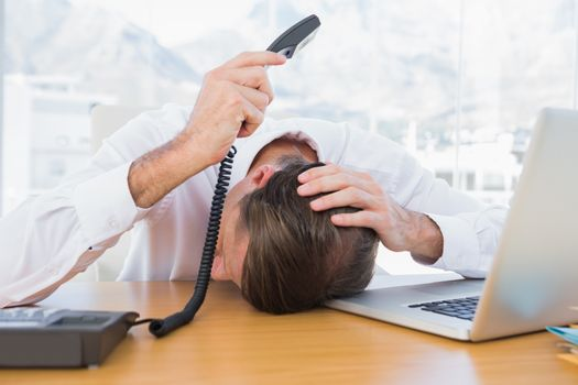 Irritated businessman holding the phone