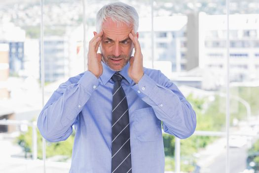 Stressed businessman rubbing his temples