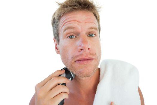 Topless man shaving his beard