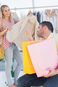 Upset man looking at his shopaholic girlfriend