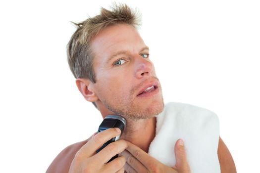 Shirtless man shaving his beard