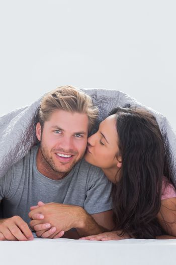 Woman kissing her husband while they are hand in hand under the duvet in bed