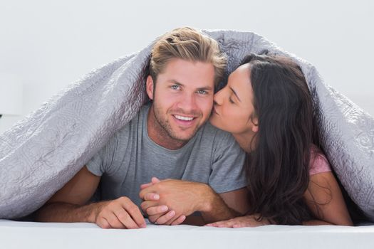 Woman kissing her husband under the duvet in bed