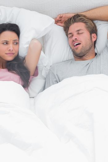 Brunette annoyed by the snoring of her husband