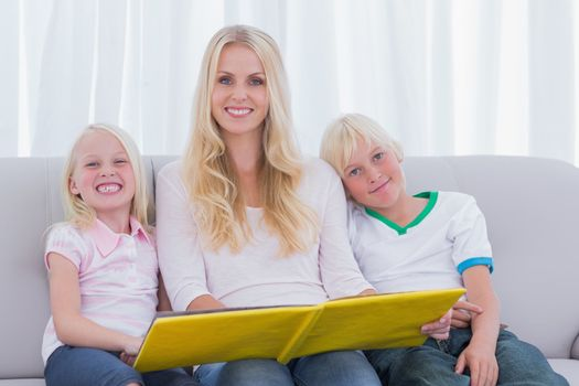 Portrait of a mother reading a story to children