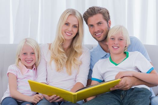 Portrait of a family holding a story book