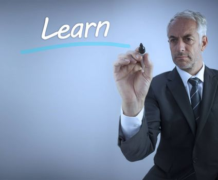 Businessman writing the word learn