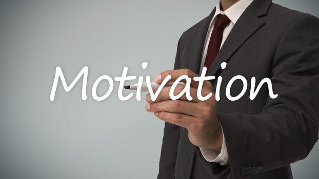 Businessman writing the word motivation