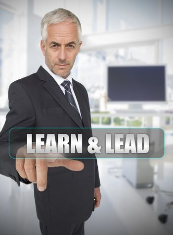 Businessman touching the term learn and lead