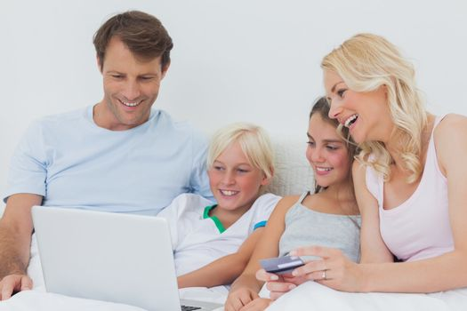 Family using computer and credit card in bed to shop online