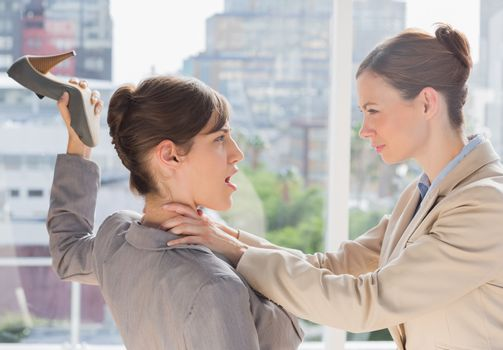 Businesswoman defending herself from her co worker strangling he