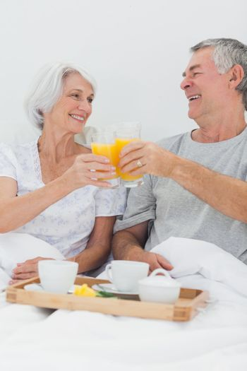 Cheerful couple clinking their orange juice glasses while having breakfast in bed