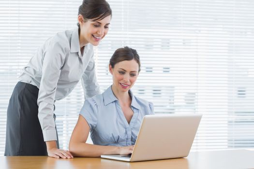 Businesswoman looking at co workers laptop