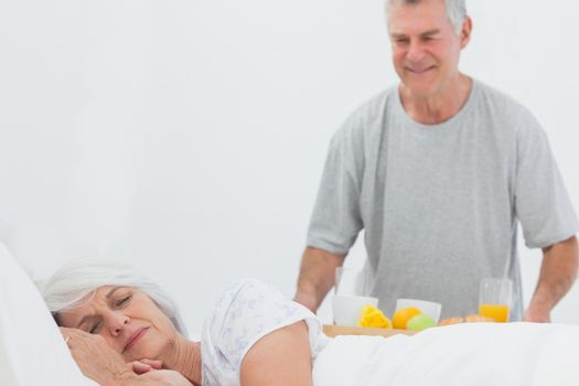 Mature man bringing sleeping wife breakfast in bed with orange juice and fruits