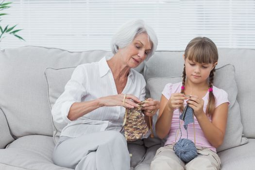 Grandmother teaching granddaughter how to knit