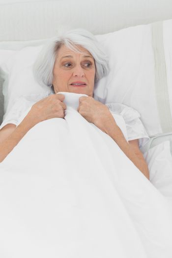 Woman looking afraid in her bed