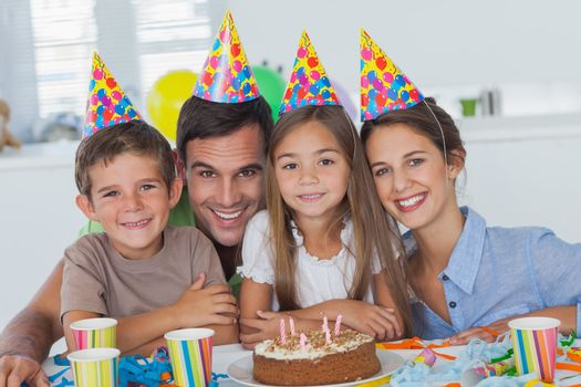 Beautiful family celebrating a party with a chocolate birthday cake