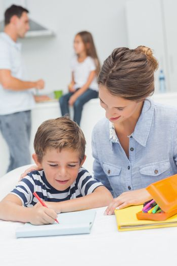 Mother drawing with her son while father is discussing with his daughter on the background