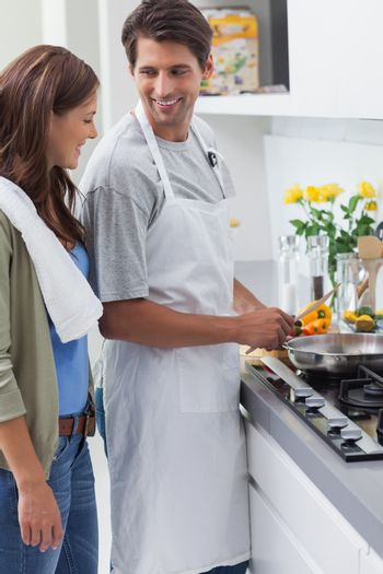 Man wearing apron and cooking
