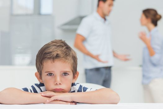 Sad boy with arms folded while parents quarreling