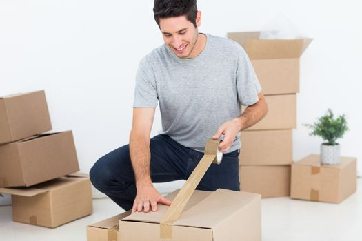 Happy man wrapping a box