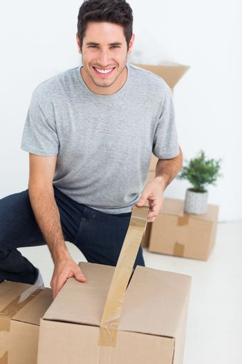 Cheerful man wrapping a box
