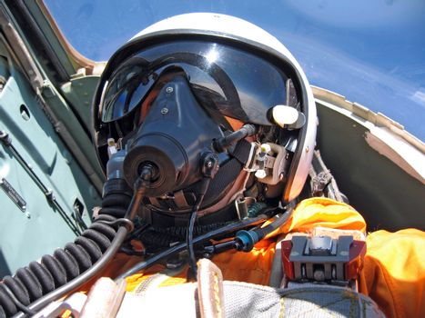 military pilot in the plane in a helmet in dark blue overalls ag