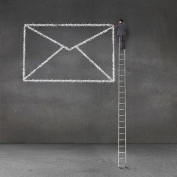 Businessman drawing a giant envelope and standing on a giant ladder
