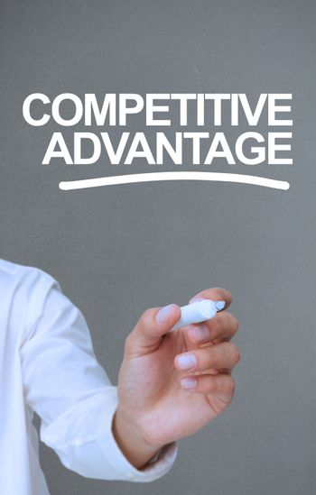 Businessman writing competitive advantage with a marker