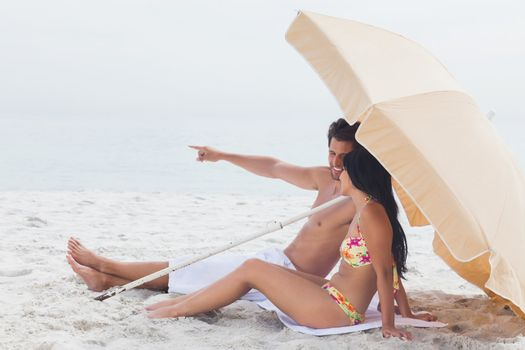 Man showing something to his girlfriend under parasol on beach