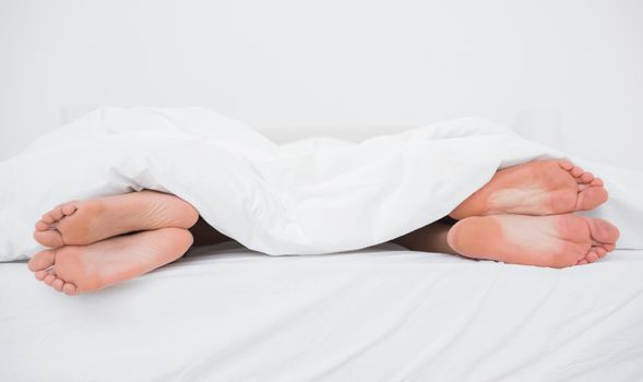 Feet of a couple on their opposite sides in bed