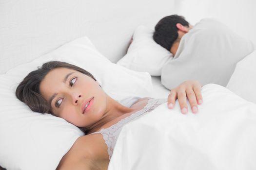 Anxious woman sleeping in bed