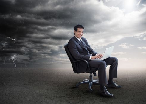 Attractive businessman using his laptop on a swivel chair outside during stormy weather