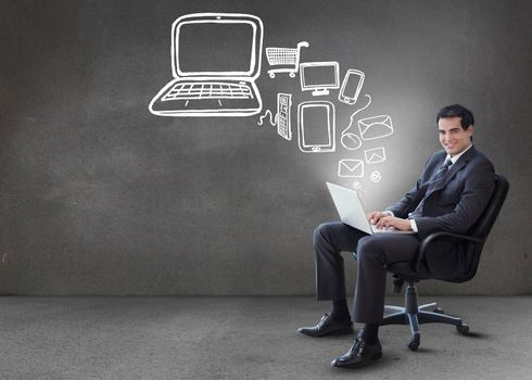 Businessman typing on his laptop with media device graphics coming from it