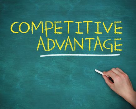 Hand holding a chalk and writing competitive advantage