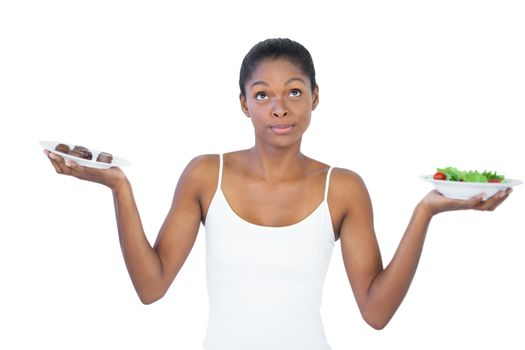 Conflicted woman deciding to eat healthily or not