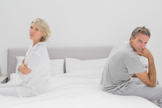 Couple sitting on opposite sides of bed looking at camera