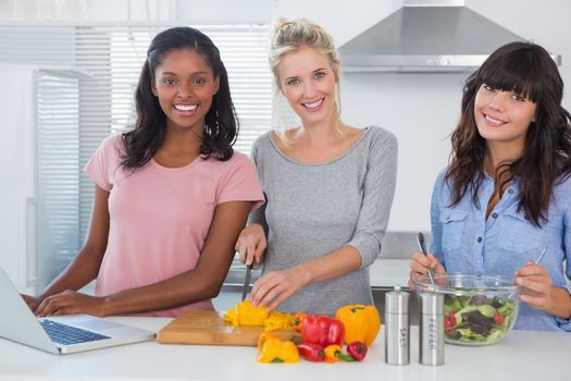 Cheerful friends making salad and using laptop for recipe looking at camera at home in kitchen