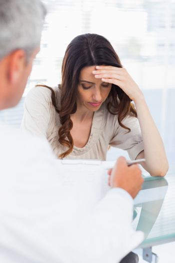 Sad woman listening to her docter talking about a illness