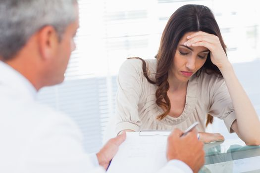 Upset woman listening to her docter talking about a illness
