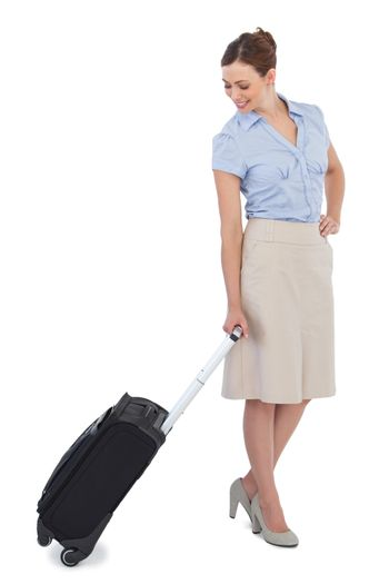Classy businesswoman carrying suitcase