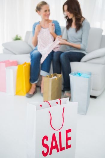 Friends with purchase and shopping bag on foreground