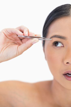 Half face of apprehensive natural woman using tweezers