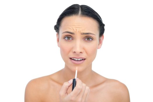 Young brunette applying lip gloss