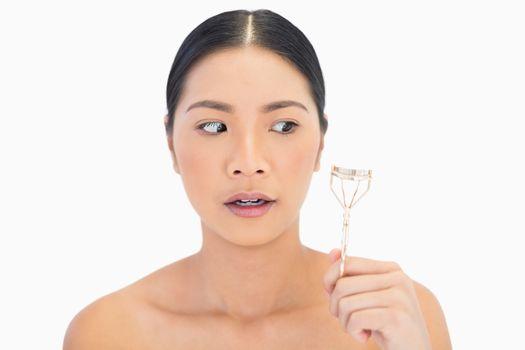 Apprehensive natural model holding eyelash curler