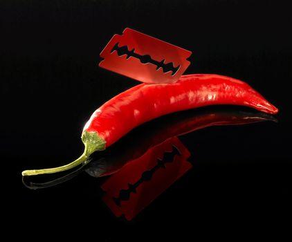 studio shot of a sharp razor blade and red hot chili in dark reflective back