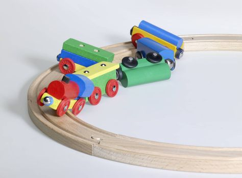 studio photography of a colorful wooden toy train and tracks while a accident happened, in light back