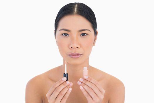 Beautiful model holding lip gloss